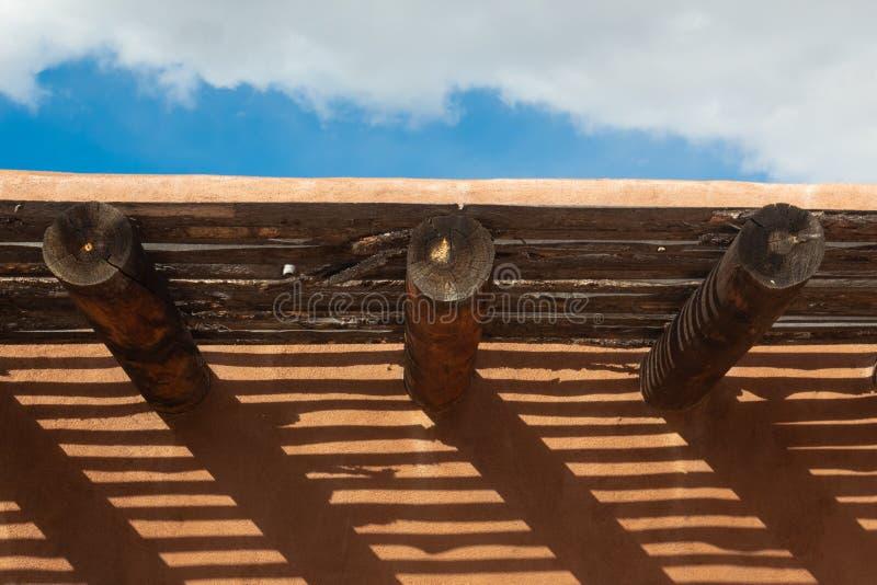 从vigas的创造性的被投下的在外部多孔黏土墙壁上的阴影和latillas 免版税库存图片