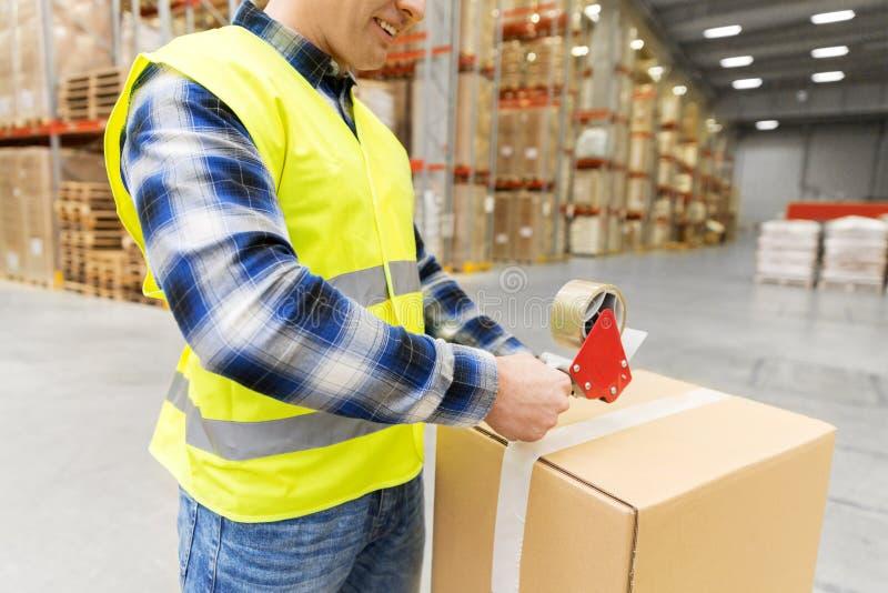 仓库工作者与透明胶带的包装小包 免版税库存照片