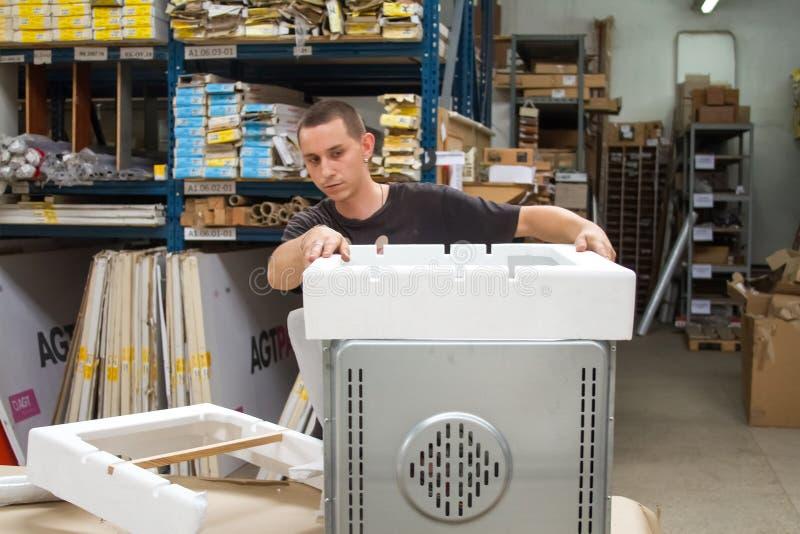 仓库工作者在发货前包装设备给顾客 免版税库存照片