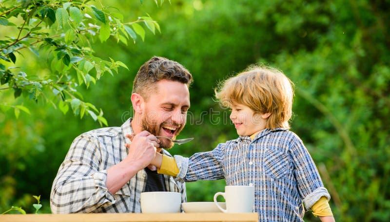 ( 他们喜爱一起吃 周末早餐父亲和儿子吃室外 小男孩孩子与 免版税库存照片