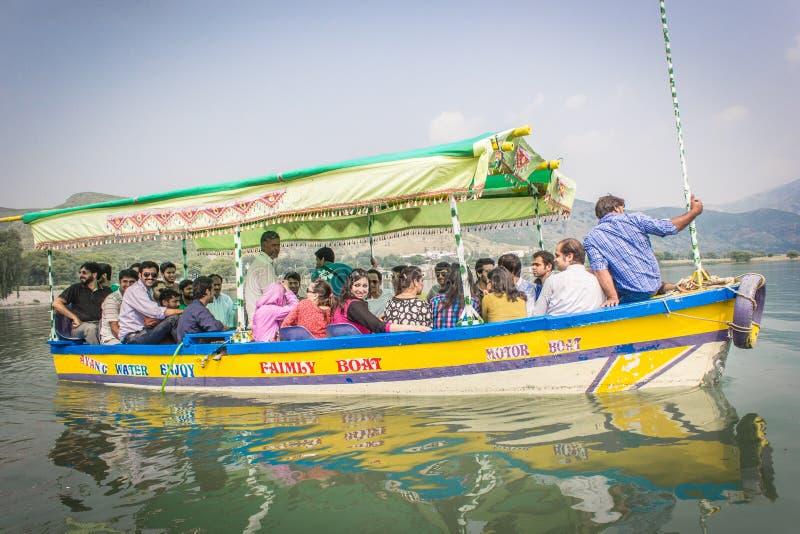 他们在湖使用这条小船搭载一次旅行的游人 库存图片