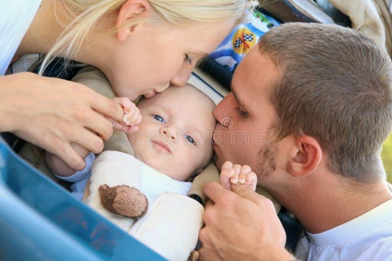 他们婴孩白种人亲吻可爱的父项的儿&# 免版税库存图片