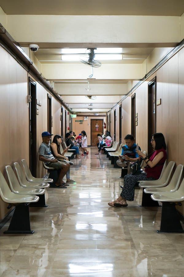 他们的手机的患者,当等待他们的医生时 库存照片