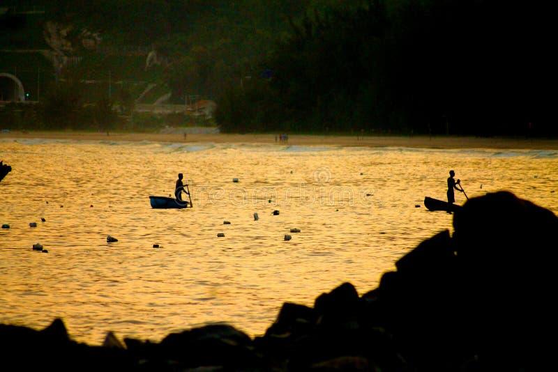 他们的篮子小船的越南渔夫在日落 库存图片