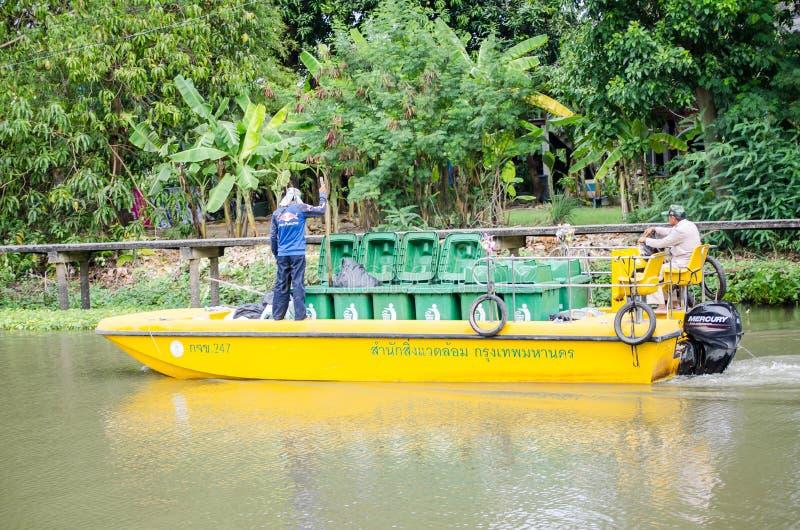 他们的黄色无用单元收集小船的一个理事会容器人在` Sansab `运河 免版税库存图片