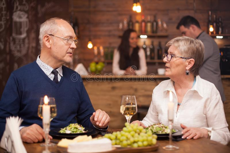 他们的60一起享受他们的时间的兄弟和姐妹,当用餐在葡萄酒餐馆时 免版税库存图片