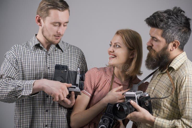 他得到了一些伟大的射击 减速火箭的样式妇女和人拿着模式照片照相机 小组有减速火箭的照相机的摄影师 库存照片