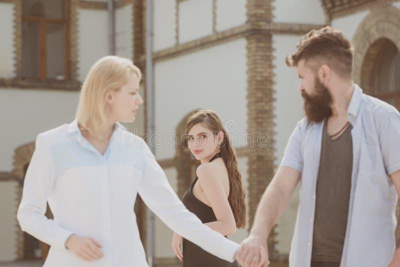 他是追逐女色的人 选择在两名妇女之间的行家 看其他女孩的有胡子的人 背叛和 库存图片