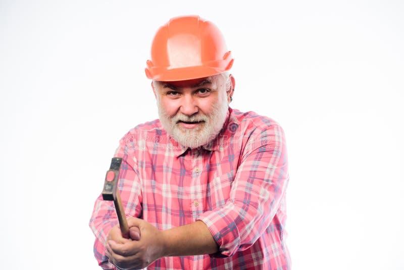 他爱他的工作 建筑修造 安全帽的成熟有胡子的人 盔甲的专业安装工 人建造者用途 库存照片