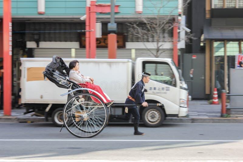 他用车运送女性顾客在日本坐独特的文化的人力车行动 免版税图库摄影