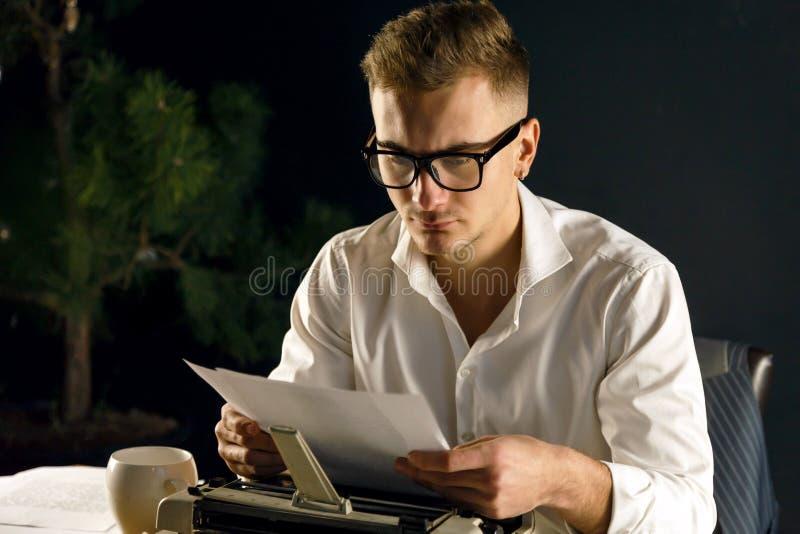 他的书作家坐的和读的新的章节  免版税库存图片