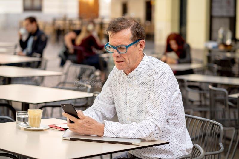 他的传送和收到在他的手机的60s的英俊的愉快的人短信在老人使用现代的人脉 免版税库存图片