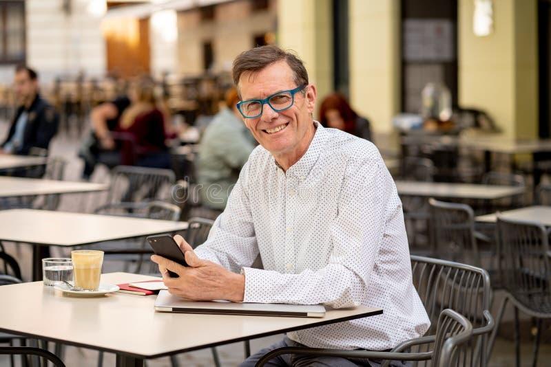 他的传送和收到在他的手机的60s的英俊的愉快的人短信在老人使用现代的人脉 免版税库存照片