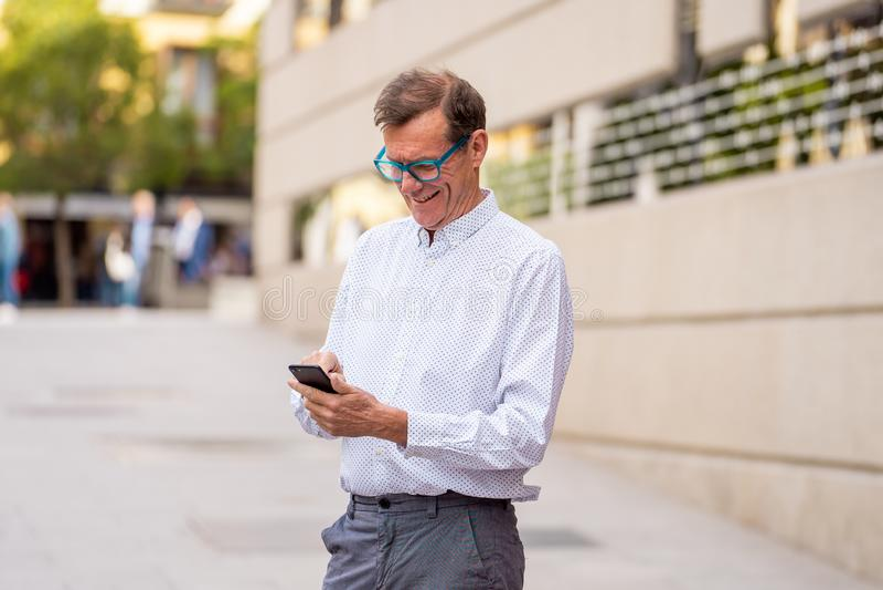 他的传送和收到在他的手机的60s的英俊的愉快的人短信在老人使用现代的人脉 图库摄影