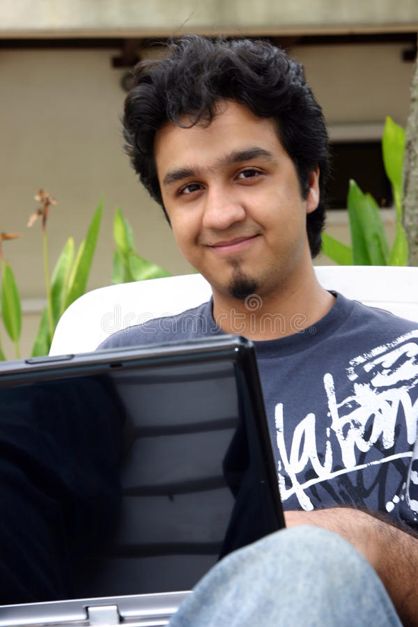 他的使用年轻人的膝上型计算机人 库存照片