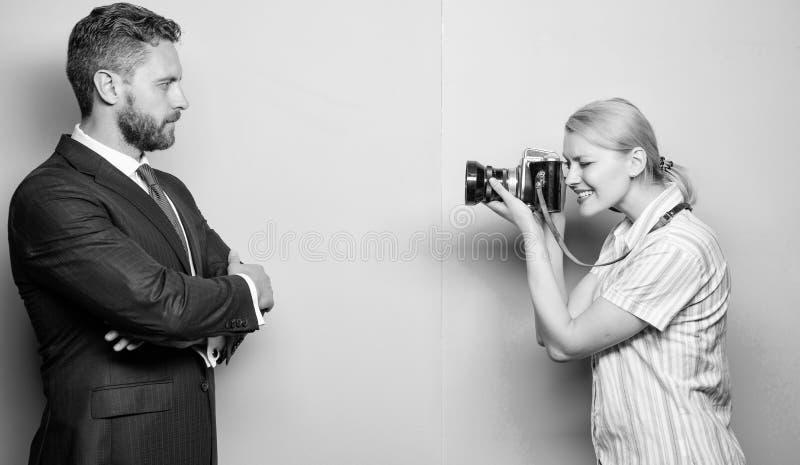 他的信心是她的焦点 摄影师射击的男性模型在演播室 摆在女性前面的商人 图库摄影