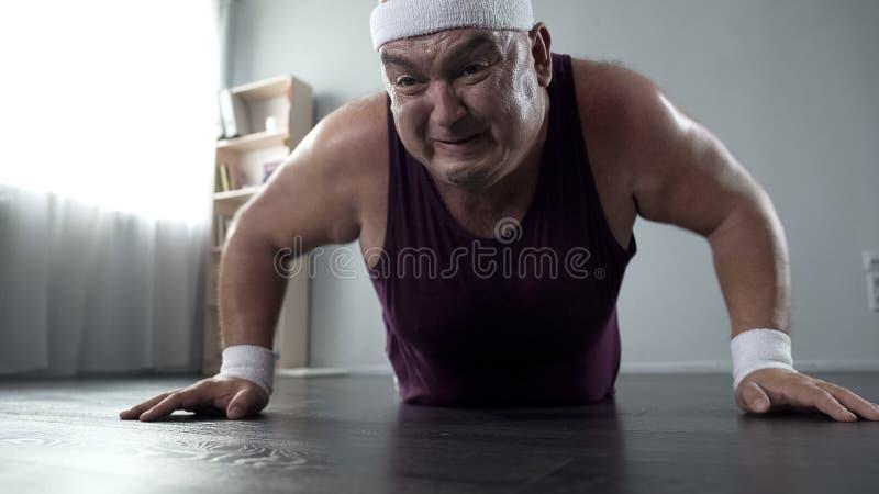他的做俯卧撑用努力,家庭训练的50s的有动机的肥满人 库存照片