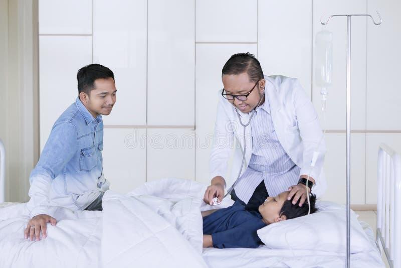 他的医生审查的病的男孩在医院 免版税库存图片