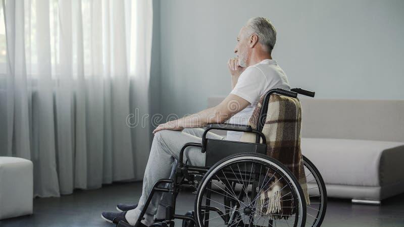 他的坐在轮椅的60s的孤独的人在健康康复中心 图库摄影