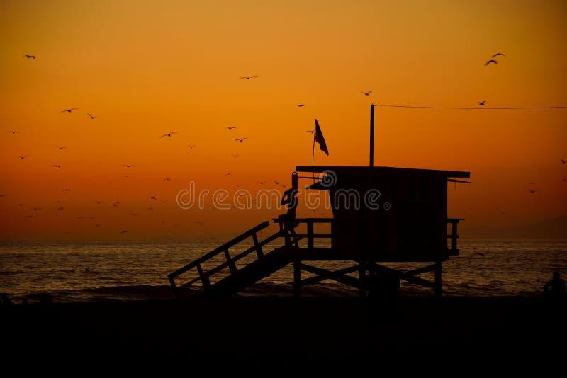 他的塔的观看海岸,在圣莫尼卡的橙色日落的一位救生员的剪影 加利福尼亚,美国 免版税图库摄影