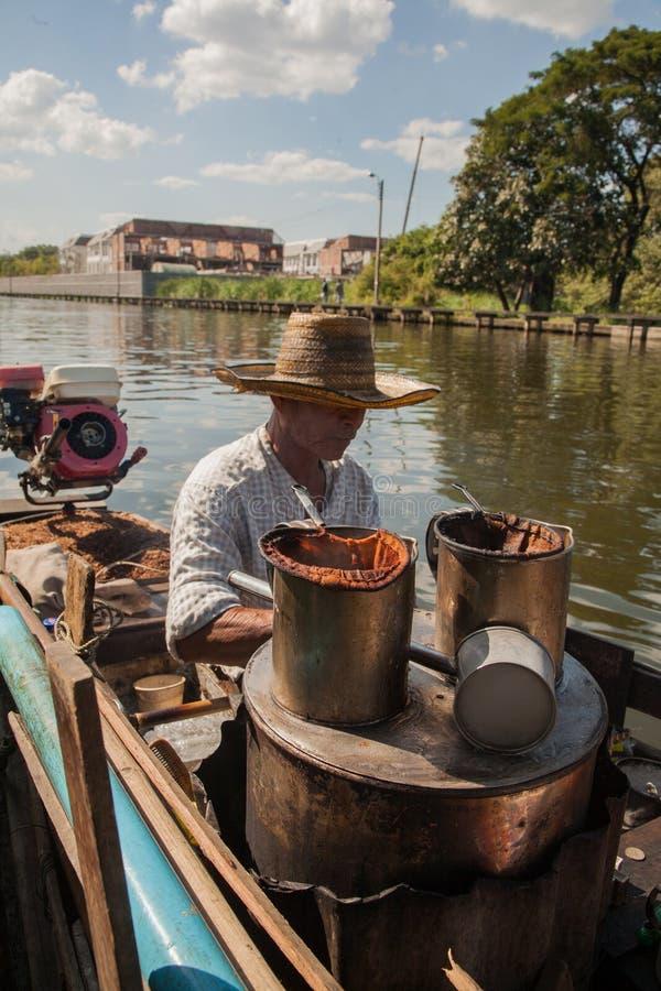他的小船的一个传统热的饮料供营商,准备在曼谷运河的一个咖啡馆 图库摄影
