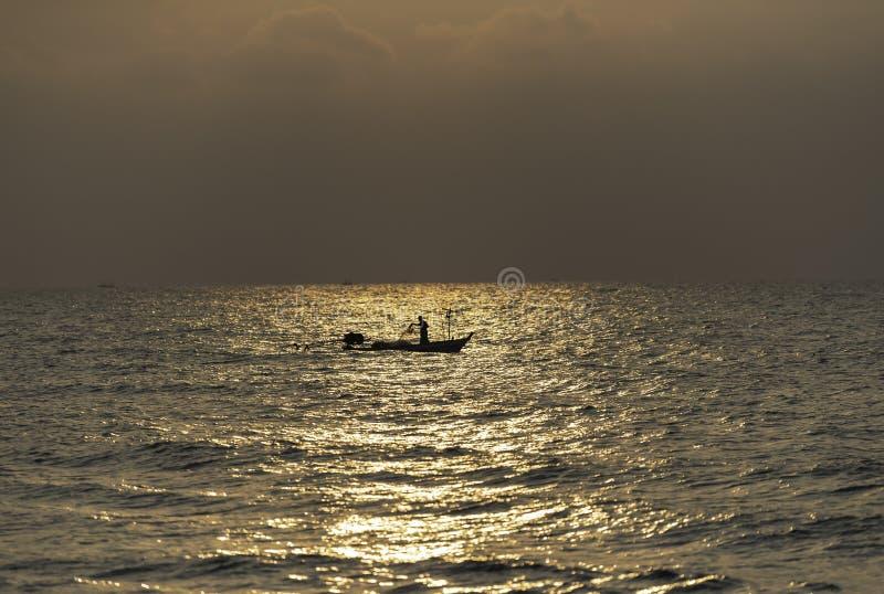 他的小船的一位渔夫有日出闪光光的  免版税库存图片