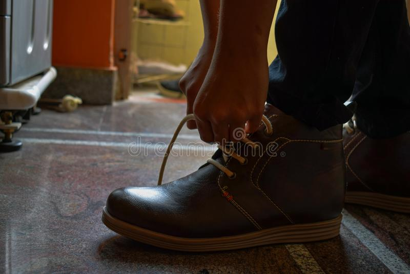 他的棕色颜色起动式样tiding的鞋带  免版税库存照片