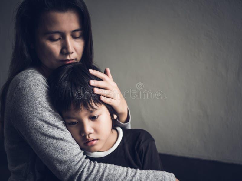他的母亲在家拥抱的哀伤的小男孩 免版税库存照片