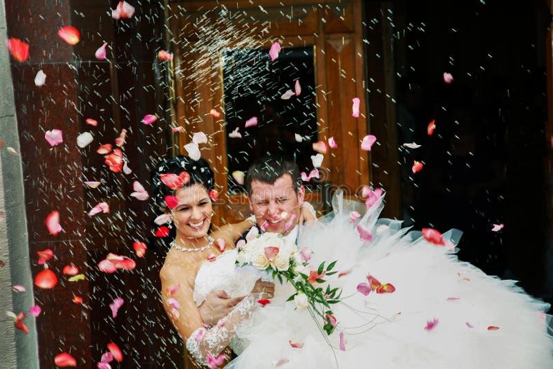 他的胳膊夫妇的新郎运载的新娘,离开管理员 免版税库存照片