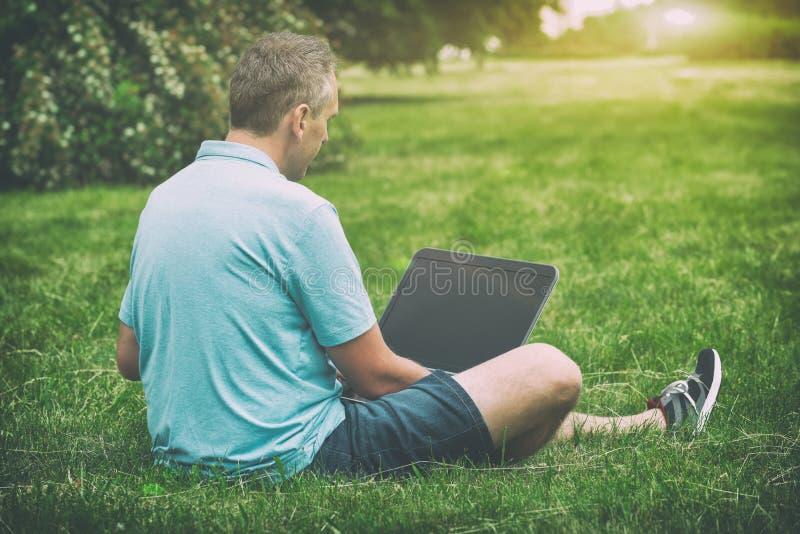 他的膝上型计算机人公园工作 免版税库存图片