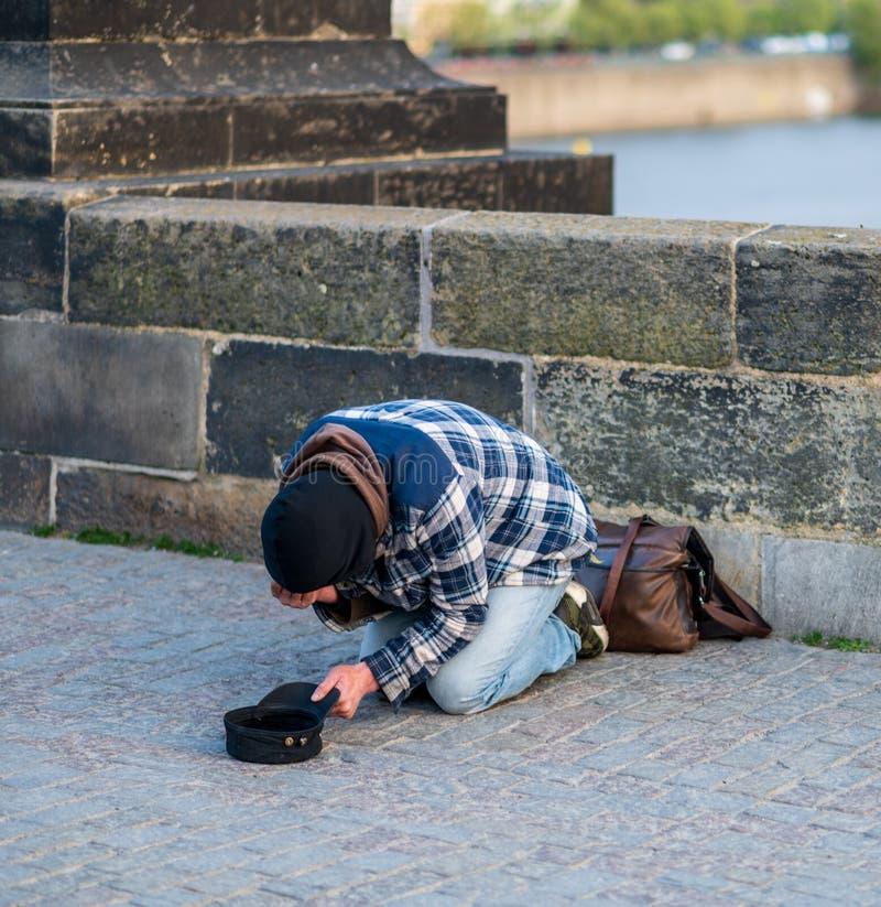 他的膝盖的冷的无家可归的人乞求为从游人的金钱查理大桥的在布拉格-春天2019年 免版税库存图片