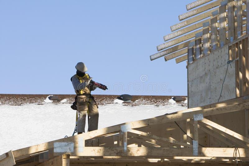 他的装载nailgun屋面防水工 图库摄影