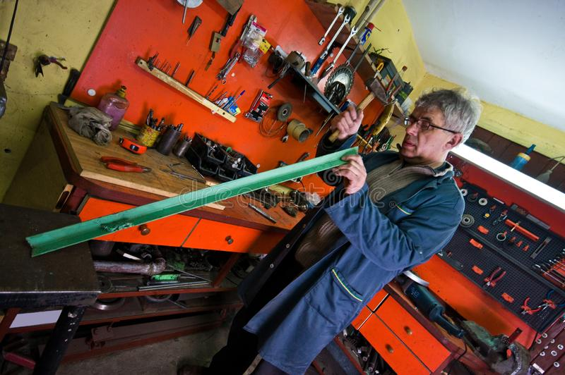他的车库的金属工,检查工具 图库摄影