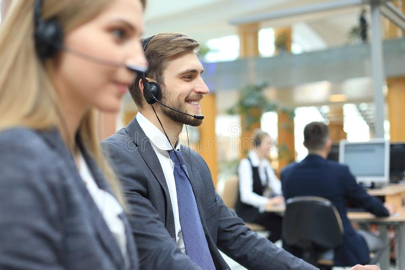 他的队陪同的电话中心工作者画象  微笑的用户支持操作员在工作 库存照片