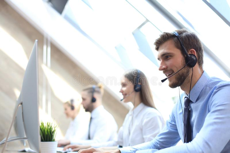 他的队陪同的电话中心工作者画象  微笑的用户支持操作员在工作 免版税图库摄影