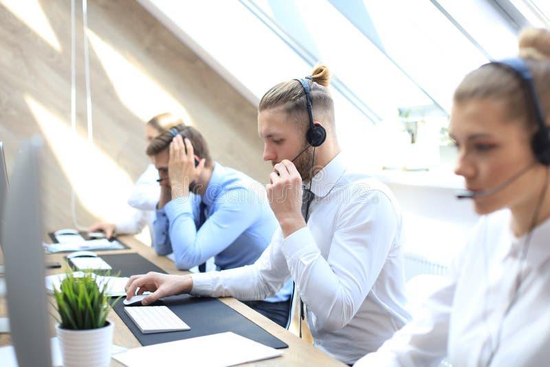 他的队陪同的电话中心工作者画象  微笑的用户支持操作员在工作 图库摄影