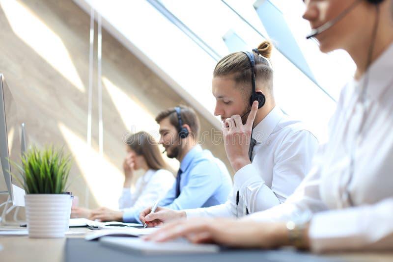 他的队陪同的电话中心工作者画象  微笑的用户支持操作员在工作 库存图片