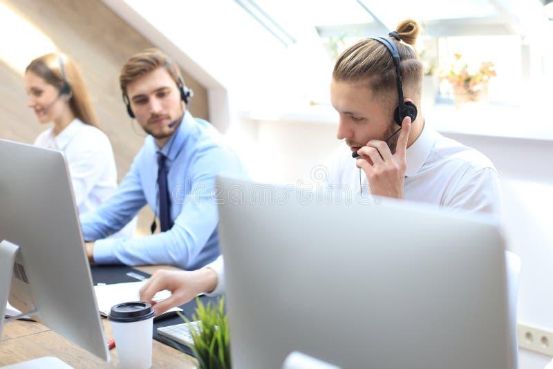 他的队陪同的电话中心工作者画象  微笑的用户支持操作员在工作 免版税库存照片