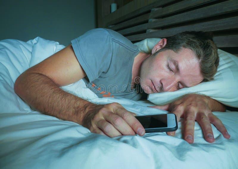他的30s或40s的可爱和英俊的疲乏的人在床上平安地睡觉和轻松在拿着在实习生的晚上手机 免版税库存照片
