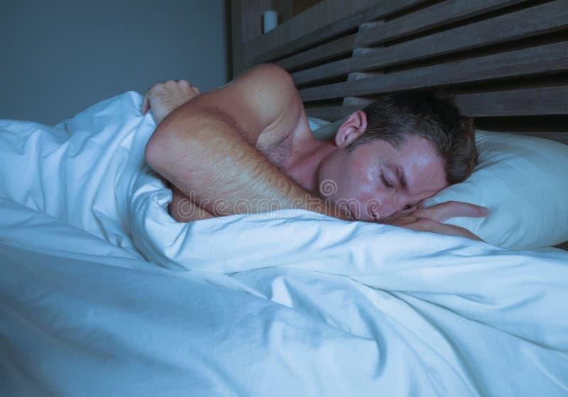 他的30s或40s的年轻可爱和英俊的疲乏的人在床睡觉赤裸上身平安地和轻松在公寓卧室关于 免版税库存照片