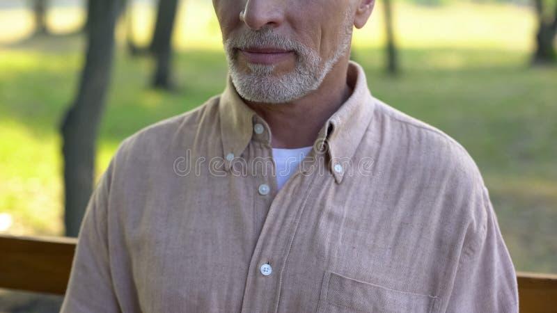 他的60s的祖父坐长凳,退休宁静在乡下 免版税库存图片