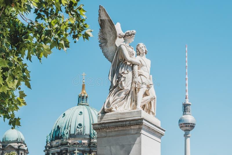 他雕象耐克协助有电视塔的Fernsehturm和柏林主教座堂受伤的战士在背景中 免版税图库摄影