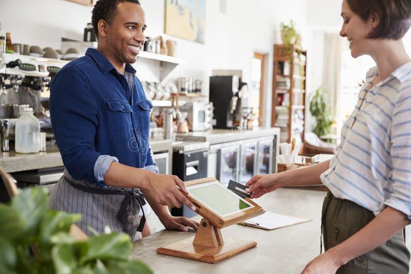 付不接触的卡片付款的女性顾客在咖啡馆 免版税库存照片