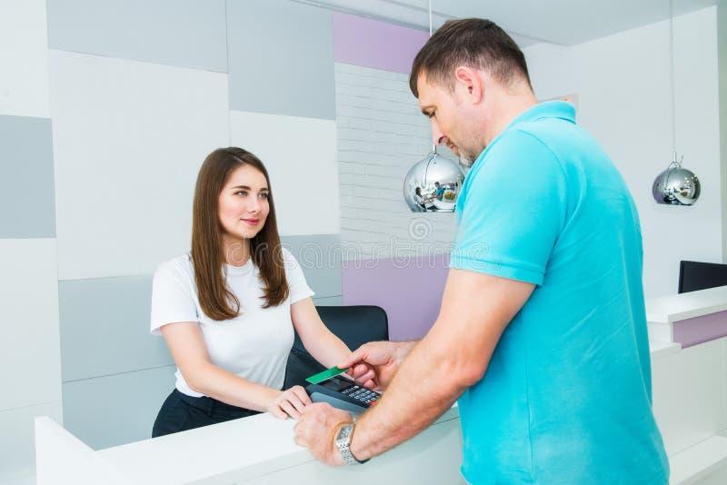 付与nfc技术信用卡的客户不接触的付款在商店,诊所,旅馆 有POS终端的行政经理 库存照片