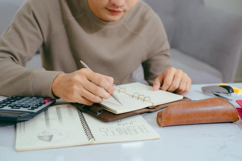 付他的帐单的被聚焦的亚裔人在客厅 免版税库存图片