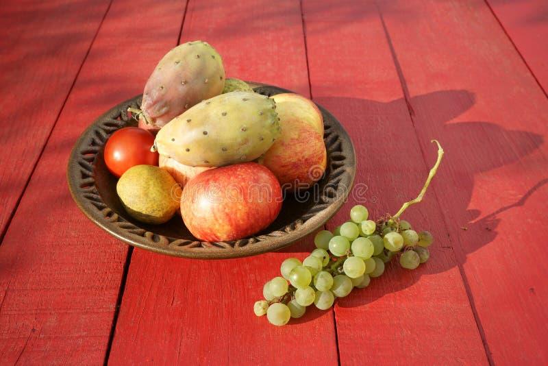 仙人球结果实,苹果,梨,在红色桌上的葡萄 库存照片