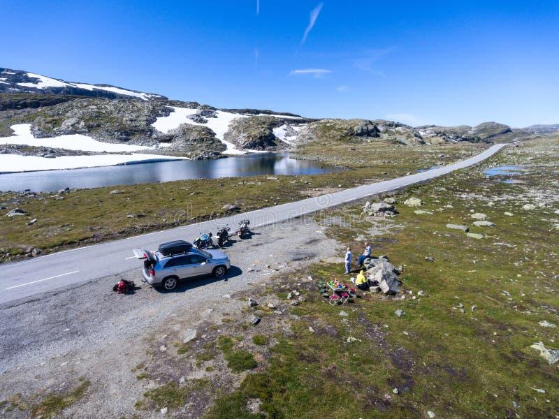 代表休息和晚餐的旅行家在山 旅行乘汽车和摩托车 挪威风景路线Aurlandsfjellet 免版税图库摄影