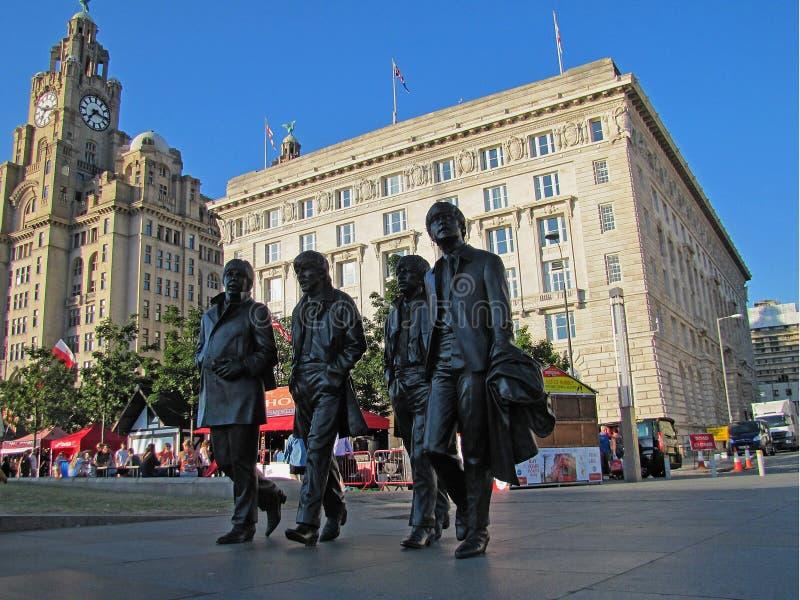 代表Beatles的古铜色雕象走沿街道在利物浦 库存照片