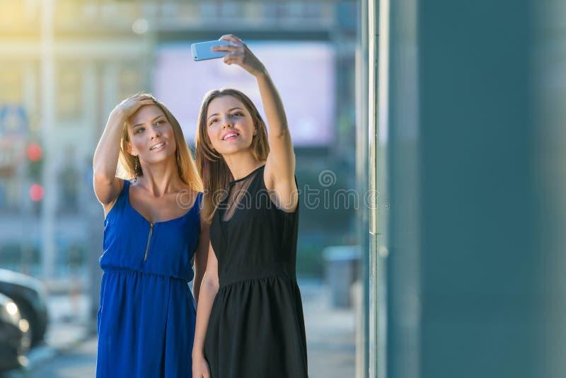 令人惊讶的年轻模型深色和白肤金发的朋友采取的Selfie 免版税库存照片