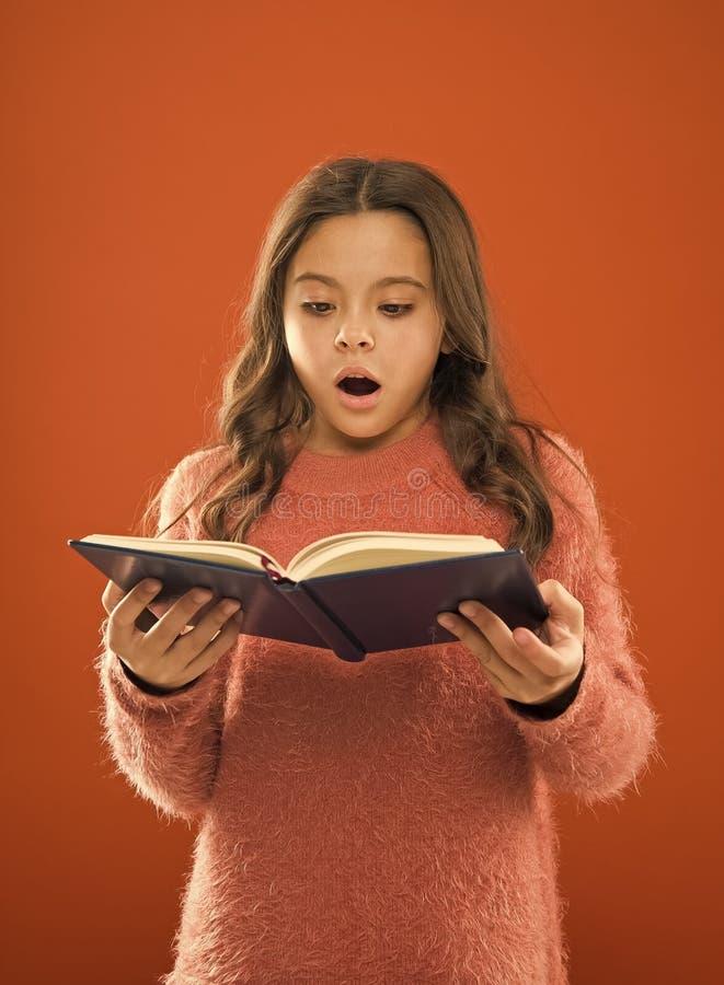 令人惊讶的故事 女孩举行书橙色背景 儿童展示书笔记薄 ?? 可利用自由的书读 库存图片